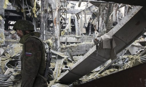 An armed man with the separatist self-proclaimed Donetsk People's Republic army stands in the destroyed terminal of Donetsk airport